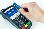 picture of plastic money  - Hand with credit card swipe through terminal for sale - JPG