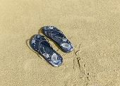 image of thong  - Cool decorated print pair of thongs in the sand.