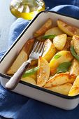 Постер, плакат: baked potato wedges in enamel baking dish