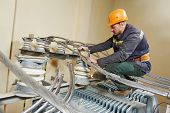 foto of lineman  - Electrician lineman repairman worker at huge power industrial transformer installation work - JPG