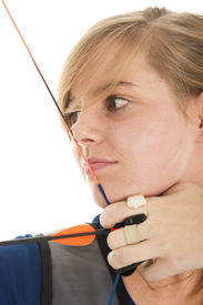 stock photo of longbow  - Young girl with blue shirt and blond hair aiming with a longbow in close up - JPG