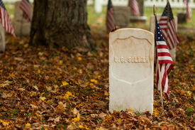 image of headstones  - An American flag next to a military headstone. Post Cemetery, Mackinac Island, MI, USA. ** Note: Visible grain at 100%, best at smaller sizes - JPG