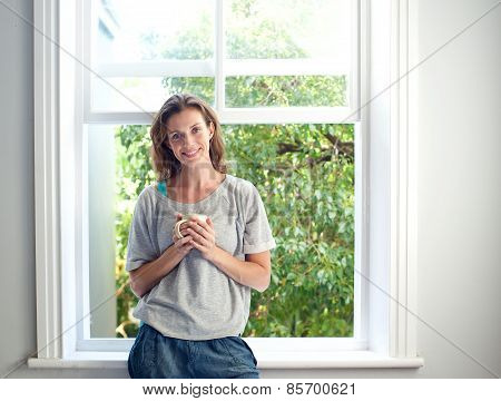 Relaxed Woman Smiling With Cup Of Coffee By Window At Home