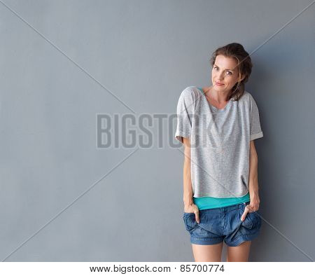 Happy Cute Mid Adult Woman Standing Against Gray Background