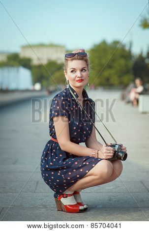 Beautiful Young Woman In Fifties Style Holding Retro Camera
