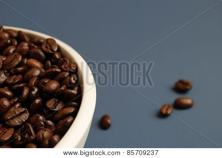 Coffee Beans in White Bowl Against Blue Background