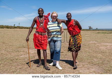 MASAI MARA,KENYA, AFRICA- FEB 12 Masai men in traditional clothes and European tourists, review of d