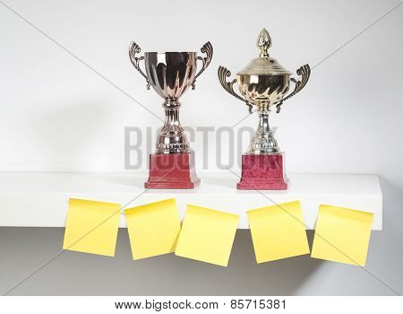 Award trophies displayed with sticky notes