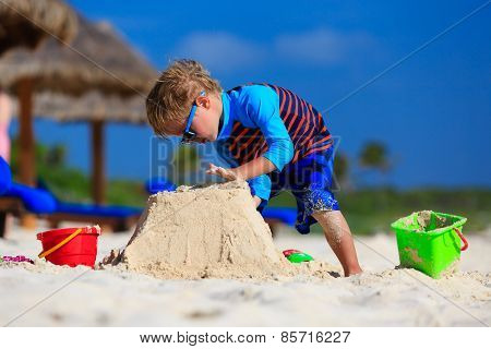 little boy building sandcastle on summer beach