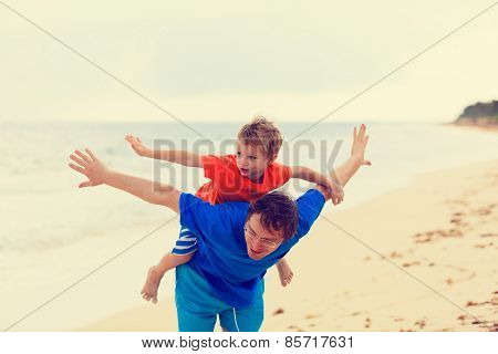 father and son flying at the beach