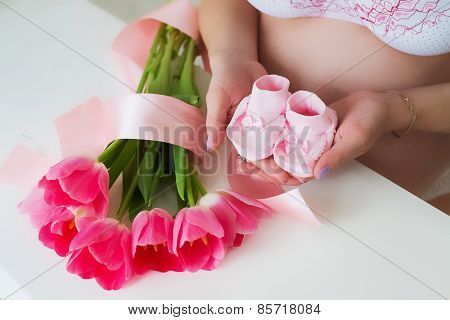 Pregnant Woman Holding Tiny Pink Child Socks In Hands With Love