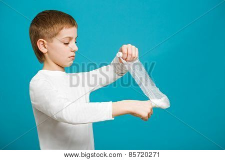 Boy In White Clothes Taping Up Bandage On His Thumb
