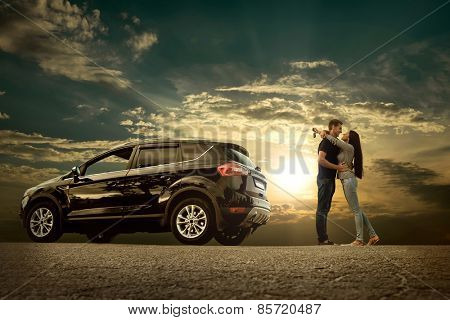 Happiness couple stay near the new car under sky