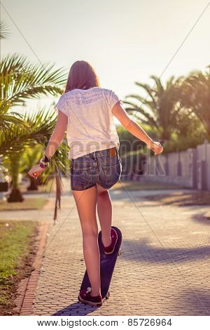 Back view of girl riding in a skateboard outdoors on summer