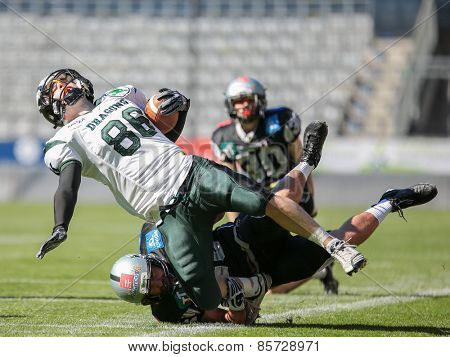INNSBRUCK, AUSTRIA - MARCH 29, 2014: WR Georg Pongratz (#86 Dragons) is tackled by LB Stefan Werner (#46 Raiders) in an AFL football game.