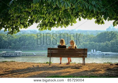 BELGRADE, SERBIA - JULY 29, 2014: two young women sitting on a bench of Kalemegdan Fortress in front the Danube rivers. Shot in 2014