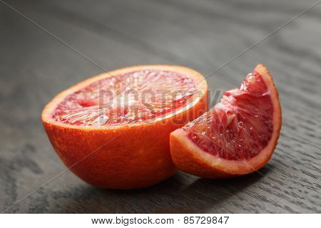 half and section of red orange on wooden table