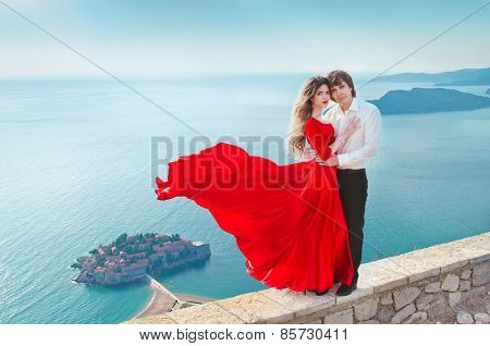 Romantic Young Couple In Love Over Blue Sea Shore Background. Fashion Girl Model In Blowing Red Dres