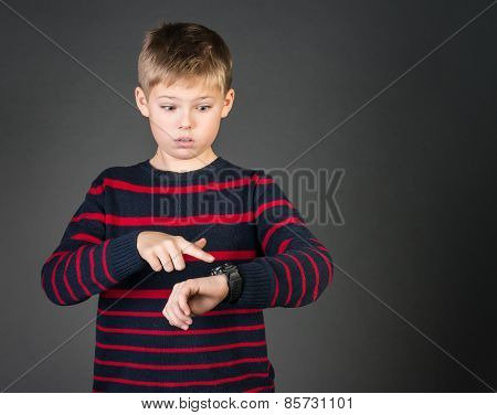 Time is money concept. Surprised schoolboy looking pointing at his watch and worried that he is late