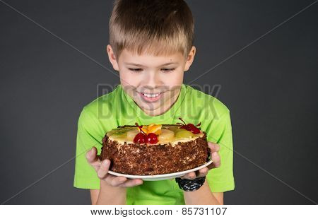Cute funny boy staring longingly at cake.