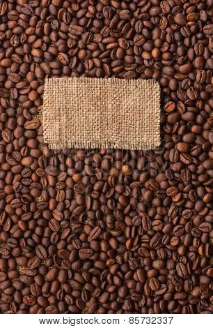 Tag Made Of Burlap Lies Against The Backdrop Of  Coffee Beans