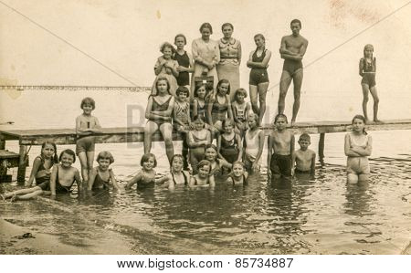 AUGUSTOW, POLAND, CIRCA 1950s: Vintage photo of group of children resting on lakeside with their tutors