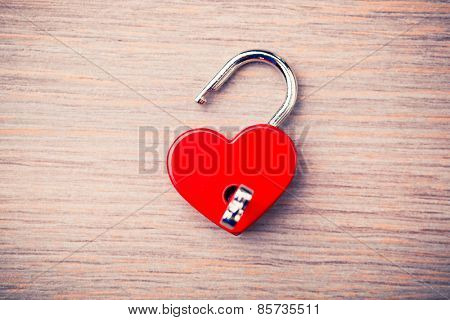 heart shaped opened lock on wooden background