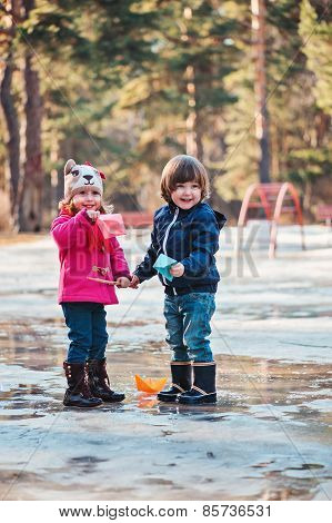 toddler boy and girl having fun playing on the walk in spring puddle with paper boats in hands