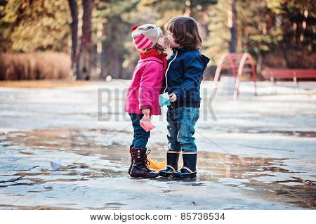 toddler boy and girl kisses on the walk in spring puddle with paper boats in hands