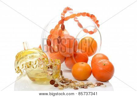 Ripe fruit tangerines in glass vase transparent and from amber necklace still life on white backgrou