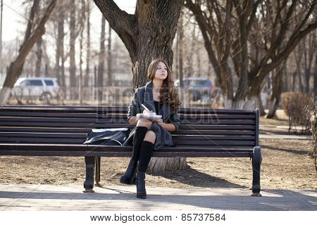 High school schoolgirl sitting on a bench with a notebook in the spring park