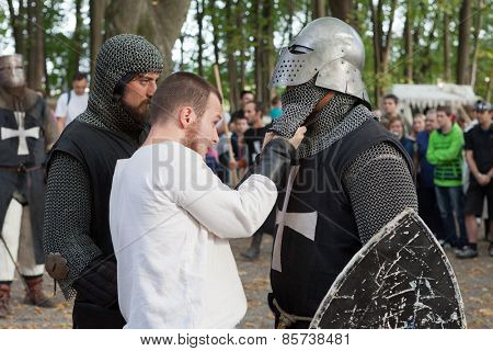 ZAGREB, CROATIA - OCTOBER 07, 2012: Squire helping knight with his helmet at
