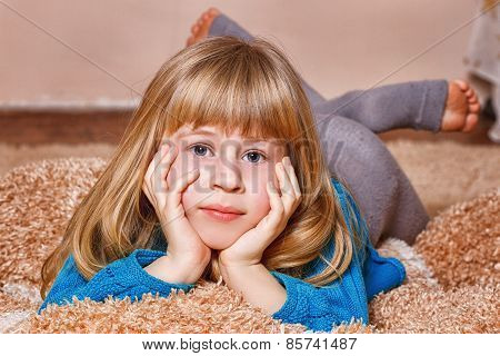 girl with funny tails is lying on the carpet