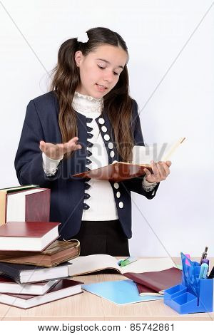 Teen schoolgirl reads textbook behind a desk with the book