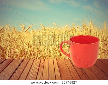Red Tea Mug On Wooden Surface Against Of Wheat Ears.