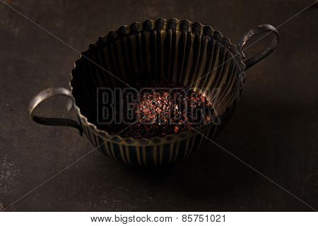 chipotle - jalapeno smoked chili flakes in small tin on metal background