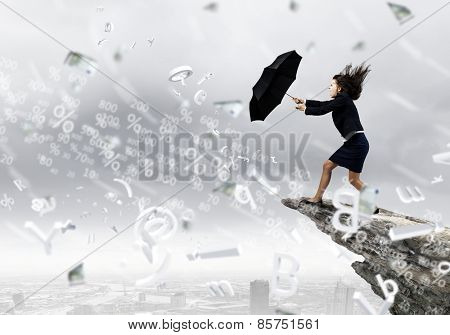 Young determined businesswoman walking against strong wind