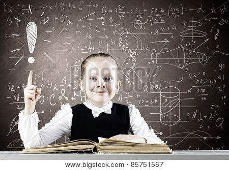 Schoolgirl at lesson with opened book against sketch background