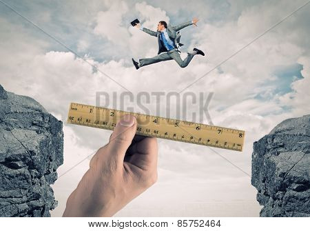 Young businessman in suit jumping over mountain gap