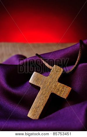 a simple wooden Christian cross on a purple drapery