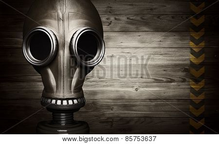 Gas mask on wooden background with sign of danger
