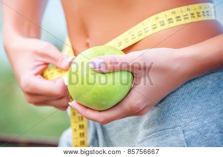 Torso of a young woman with an apple and meter