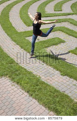 Young Woman Leaping Over a Grass Maze