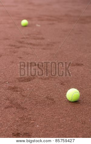 Two green tennis balls on the clay court