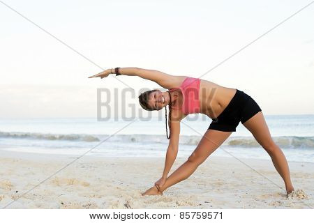 Woman practicing yoga at the beach - triangle pose