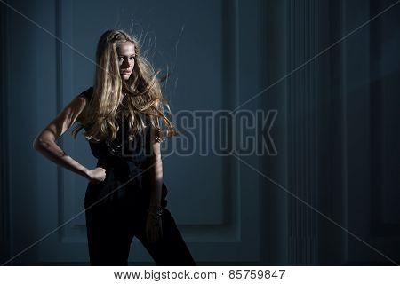 Studio portrait of long-haired model on a dark background with f