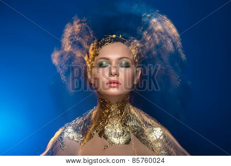 Close-up portrait girl model in a stylish gold foil. Blurred mar