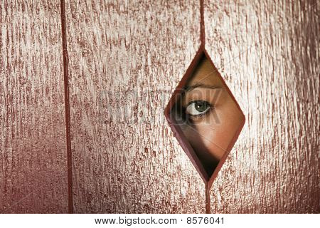 Woman Looking Through a Hole in the Wall