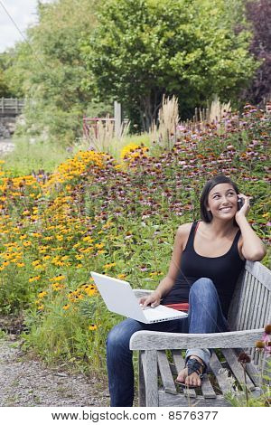 Young Woman Using Laptop and Cellphone on a Park Bench