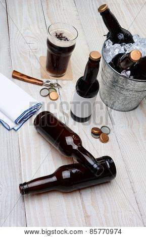 High angle shot of a party bucket filled with beer bottles on a rustic wood table. Empty bottles and bottle caps are on the table along with a glass of dark ale and bar towel.